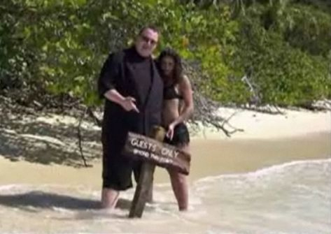 "Kim Dotcom, with a lady and a sign. The sign reads ""guests only"". Presumably the lady is a guest."