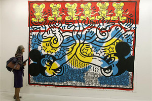 Lady looks at unnamed Keith Haring painting