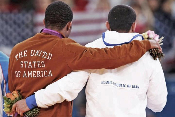 USA's Jordan Burroughs with his arm around Iran's Sadegh Saeed Goudarzi. Photo: Mike Hughes, ‏@mikehughescq