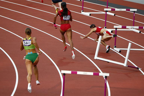 Bulgaria's Vania Stambolova crashes into a hurdle as Lithuania's Egle Staisiunaite and T'Erea Brown of the US run in the women's 400m hurdles round 1 heat during the London 2012 Olympic Games at the Olympic Stadium. Photo: Reuters